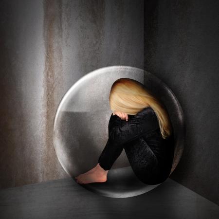 femme triste: Une jeune femme est d�prim�e et triste dans une bulle dans une pi�ce sombre La jeune fille a la t�te en bas et se blottit dans un coin