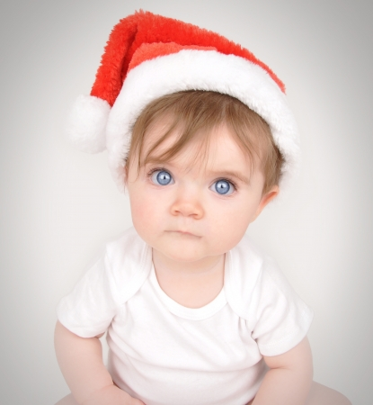 A little baby is sitting down and looking into the camera with big blue eyes and a santa christmas hat on Stock Photo - 17344902