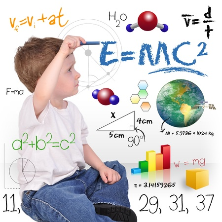 A young boy child is writing out math and science equations and formulas  He is sitting on the floor on a white background  Use it for a school, study or learning concept  photo