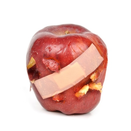 A red apple has a band-aid over with cut and bruised pieces on a white isolated background