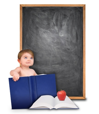 A young baby is holding a book and looking up at a blank black chalk board  There is an open book with an apple for school  Add your text message in the copyspace  Stock Photo - 17348379