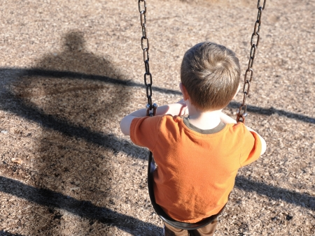 terror: A young boy is sitting on a swing set and looking at a shadow figure of a man or bully at a playground  Use it for a kidnap or defense concept  Stock Photo