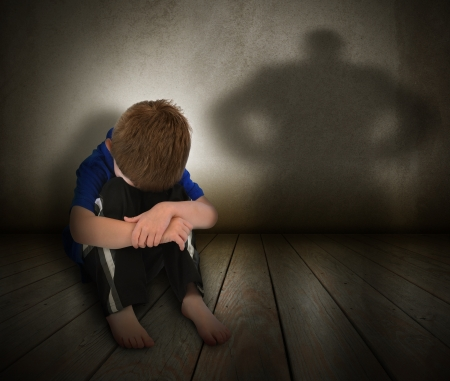 threatened: A young boy is sitting on the ground and scared with his face covered  There is a shadow silhouette on the wall to represent abuse, fear, or a bully  Stock Photo
