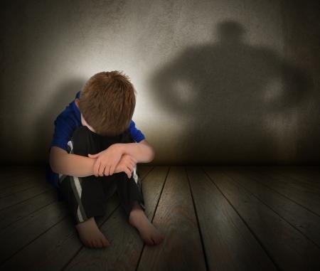 maltrato infantil: Un joven está sentado en el suelo y asustado con el rostro cubierto Hay una silueta sombra en la pared para representar el abuso, el miedo, la intimidación o la