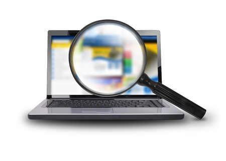 A computer laptop is isolated on a white background with a magnifying glass searching the internet