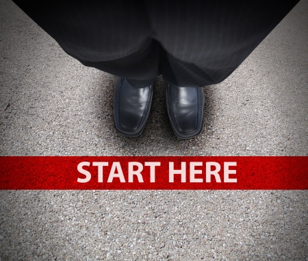 start position: A business man is looking down at his feet with a red race line that says start here to represent a journey