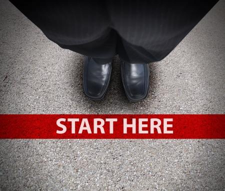 start of race: Un hombre de negocios est� mirando hacia abajo a sus pies con una l�nea de carrera rojo que dice empezar aqu� en representaci�n de un viaje