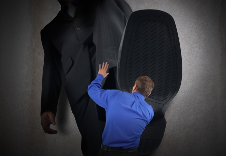 A little business man is under a big bosses foot about to crush or step on him  His hands are in the air scared  photo
