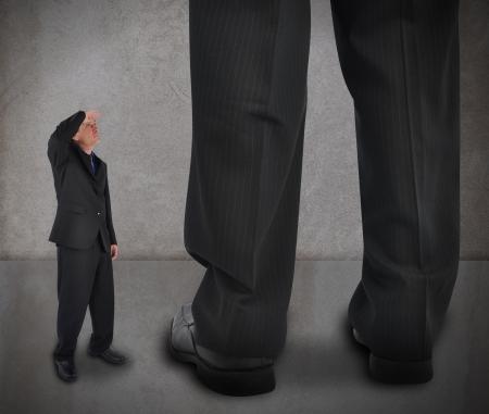 obstaculo: Un hombrecillo pequeño negocio está mirando a un gran jefe grande en un fondo de textura Utilícelo para un concepto de alimentación o desafío