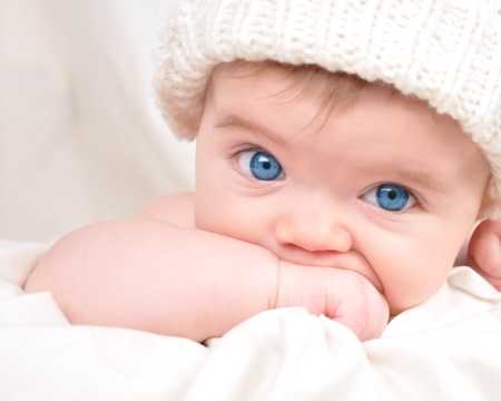 A young child is looking into the camera and sucking their hand  The baby is wearing a hat and has bright blue eyes  Use it for a parenting or love concept