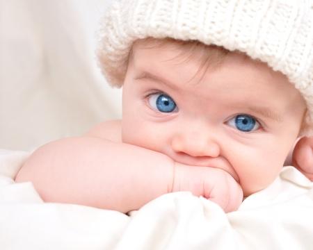 Un jeune enfant se penche sur la caméra et sucer leur main Le bébé porte un chapeau et a les yeux bleus lumineux Utilisez-le pour un concept parental ou de l'amour