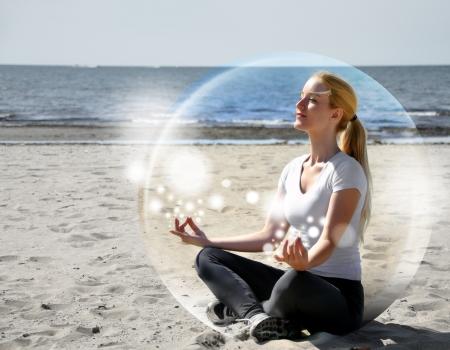 persona respirando: Una mujer está sentada en la playa dentro de una burbuja de paz y tranquilidad que está meditando y hay destellos