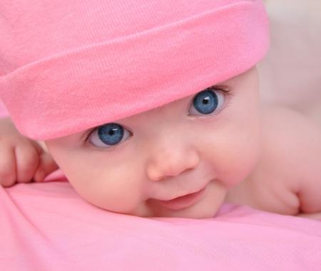 Una niña linda bebé está mirando y está en una manta de color rosa Ella lleva un sombrero de color rosa y tiene grandes ojos azules Utilícelo para un concepto de niño, los padres o el amor Foto de archivo