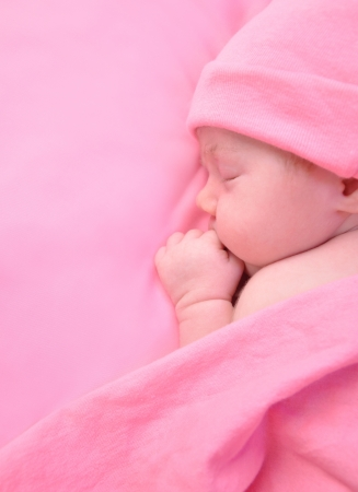 newborns: A newborn baby girl is sleeping on a pink blanket and is wearing a hat  Use it for a childhood, parenting or innocence theme  Add your text message to the side