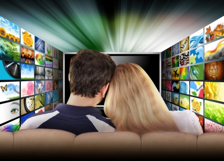 out of date: A couple is sitting on a couch watching a flat screen television with photo images coming out of the sides  The tv has a glowing light coming out the top  Use it for a media, entertainment, technology or date night concept  Stock Photo