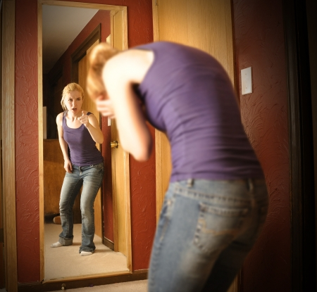 A young woman is depressed looking in a mirror while the reflection is yelling an pointing at her self in anger. Banco de Imagens