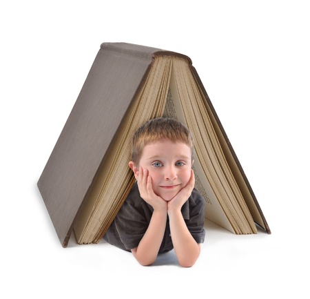 scholastic: A little boy is lying under a big large book on a white isolated background for an education or reading concept.