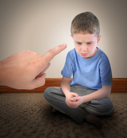 A sad little boy is getting a time out with a finger pointing at the child for a discipline parenting concept.  photo