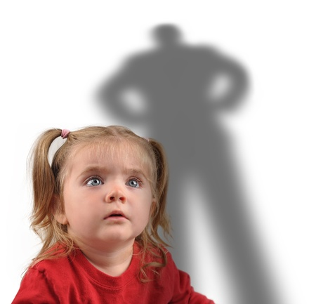 protect: A little girl is looking up at a scary shadow of a man on a white background for a fear or kidnapping concept.