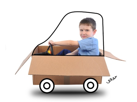 A young boy is driving a box car with a wheels thar are drawn and he is holding a steering wheel on a white background