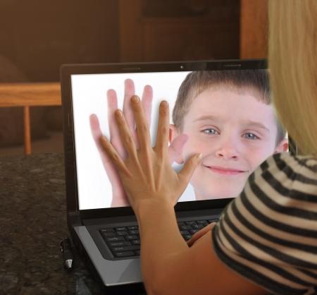 母は web カム通信笑みを浮かべて彼女を彼女の幸せな息子とラップトップ コンピューターの画面に触れること