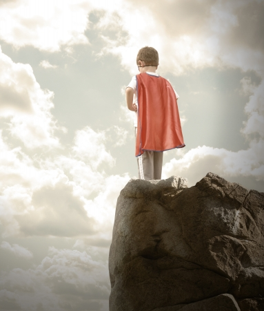 A young super hero boy is wearing a red cape and standing on a rocky cliff looking at a cloudy sky with copyspace
