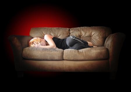 hoofdpijn: Een meisje legt op een bank triest met depressie en lichamelijke pijn