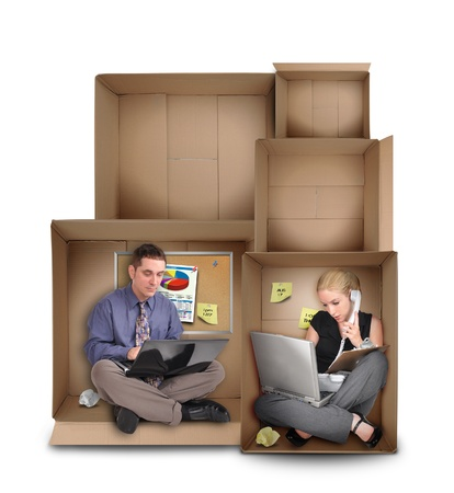 Two business people are working in cardboard boxes with empty spaces above them