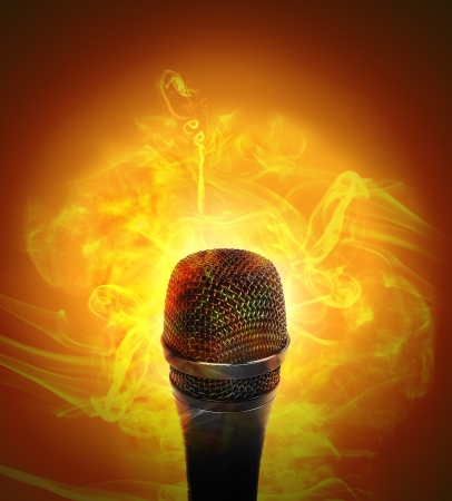 A microhone has fire smoke around it on an orange background for a music or entertainment concept  photo