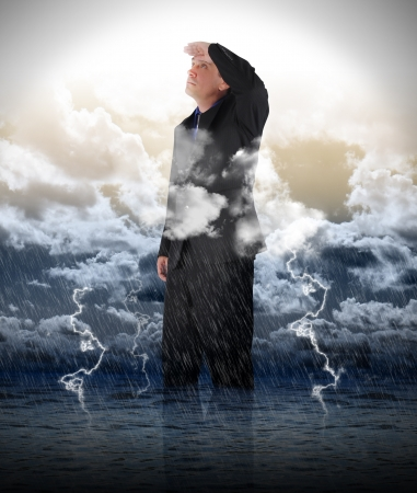 business metaphore: A business man is looking up to bright light in stormy weather for a strength, success or faith metaphore   Stock Photo