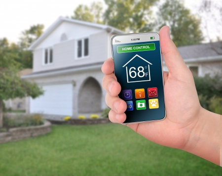 mobile app: A smart phone is in front of a house with various home control icons like temperature and time