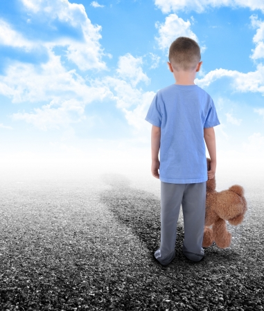 A young boy is holding a teddy bear and standing on an empty road with clouds in the sky photo