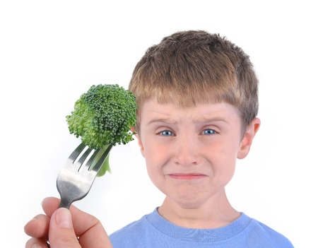 A young boy is making a funny disgusting face at a fork with a healthy piece of broccoli on a white background.  Stock Photo - 18546546