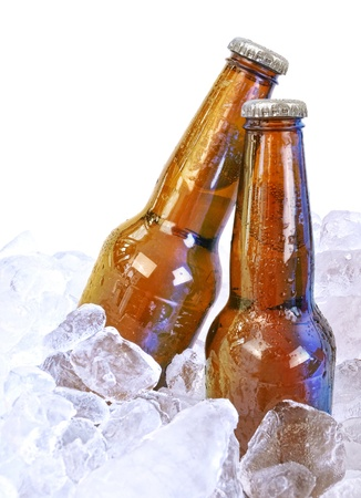 Two moist beer glass bottles are isolated on a white background with ice cubes around them for a party or bar concept. photo