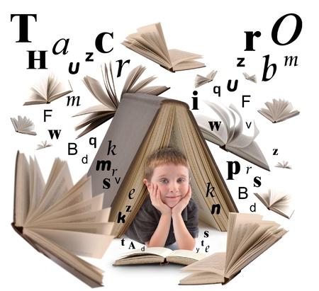 lezing: Een kleine jongen is onder een groot boek op een witte achtergrond geïsoleerd voor een opleiding of lezen concept. Er zijn brieven zweven om hem heen. Stockfoto