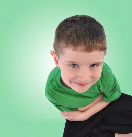 A happy young child is sitting down looking up on an isolated green background with copyspace. The boy is thinking. photo