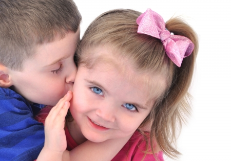 A little boy is kissing his kid sister on the cheek on a white isolated background for a child love concept. Stock Photo - 19405261