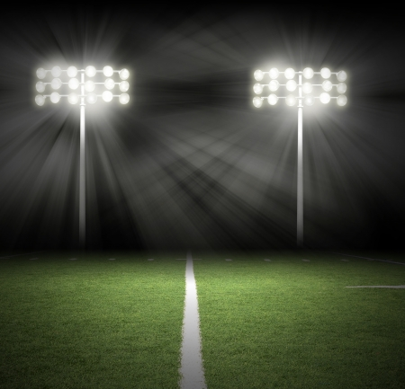 soccer field: Two Stadium football game lights are shinning on a green grass field for a sport concept.