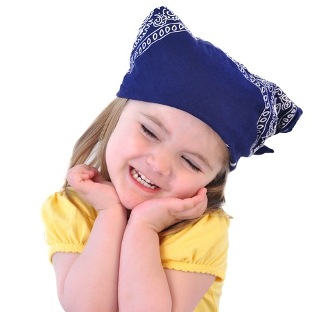 A little girl is smiling with a yellow shirt and blue bandana on an isolated white background for a happiness concept. photo
