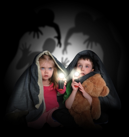 stories: Two little children are hiding under a blanket looking at black scary monster ghosts in the background with flashlights.