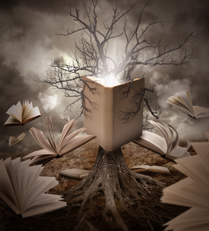 A tree with roots is reading a story with books floating around it on a brown old landscape. photo