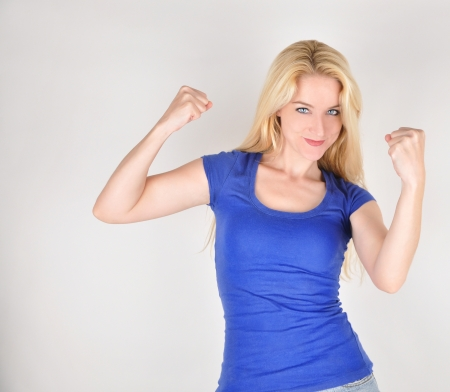 defense: A happy beautiful girl is holding up her strong muscles on an isolated background to show confidence and strengh. Stock Photo