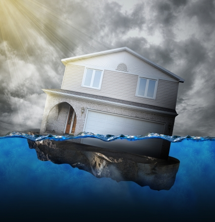 derrumbe: Una casa se está hundiendo en el agua por una deuda hipotecaria o concepto de desastres naturales. Foto de archivo