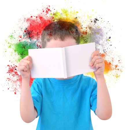 A young boy is holding a blank white book with colorful rainbow paint splatters coming out on a white isolated background.