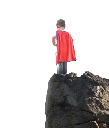 A young hero boy is wearing a red cape and standing on a rocky cliff looking at a white isolated background