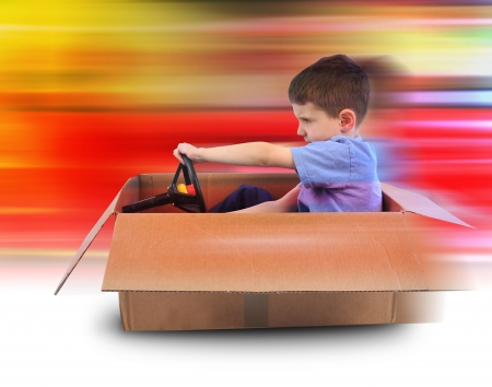 A young boy is driving in a cardboard box with red speed lines in the background photo