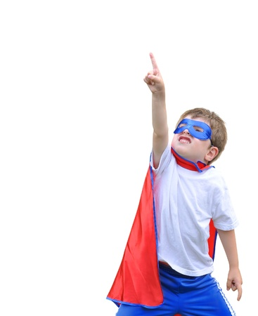 A young boy is dressed up as a superhero and pointing up with a mask and cape