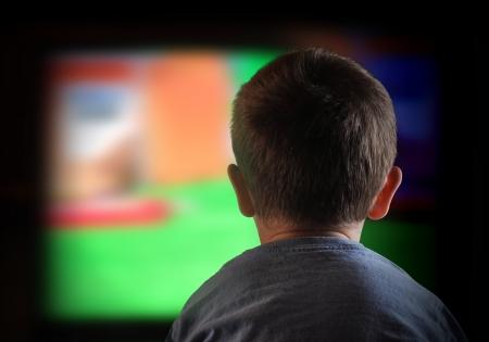 어린 소년은 TV 화면을 지켜보고있다 스톡 콘텐츠