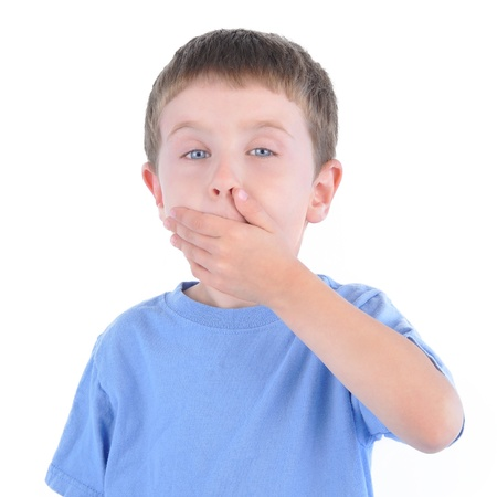 A young boy is holding his hand over his mouth for silence and not talking on a white background.  photo