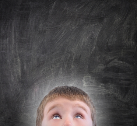 A young school boy is looking up at a blank black chalkboard